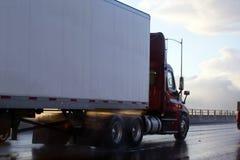 Rimorchio del camion dei semi della carrozza di giorno nella riflessione del sole e della pioggia Fotografie Stock Libere da Diritti