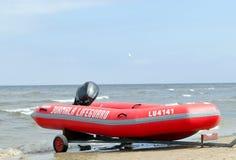 Rimorchio di gomma della barca del bagnino sul puntello di mare Fotografie Stock