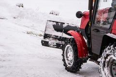 Rimozione di neve nell'inverno il trattore Pulendo le vie di neve con un trattore fotografia stock libera da diritti