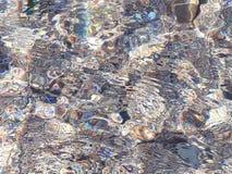 rimpelingen en bezinning van de zon op de rotsachtige bodem van het water royalty-vrije stock fotografie