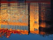 Rimpelingen op de oppervlakte van het meer dat op het high-tech gebouw wijst Stock Foto