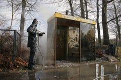 Rimuovendo i graffiti dalla fermata dell'autobus fotografia stock