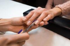 Rimuovendo la cuticola dalle pinze del manicure Fotografie Stock Libere da Diritti