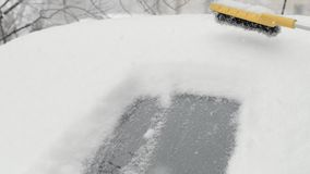 Rimuovendo neve da una finestra di automobile facendo uso di una spazzola Spazzolatura del parabrezza da neve archivi video