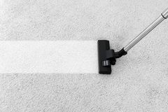 Rimuovendo sporcizia dal tappeto molle con l'aspirapolvere immagini stock