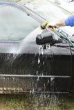 Rinçage de la carrosserie avec de l'eau d'un tuyau d'arrosage Photo stock