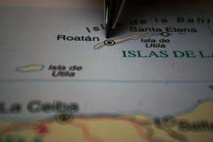 Rinchiuda indicare su una mappa un'isola Roatan dell'Honduras immagini stock libere da diritti