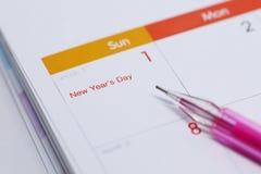 Rinchiuda l'orario di lavoro di scrittura sul calendario da tavolino del 1° gennaio 2017 Fotografia Stock
