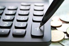 Rinchiuda la stampa sul calcolatore più del bottone e le monete sulla tavola della scrivania Fotografia Stock