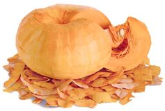The rind of the pumpkin isolated. A piece of peeled cut from a whole fruit ripe orange pumpkins with white seeds. Horizontal close-up lies in the removed peel stock photography