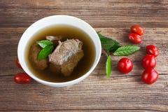 Rinderbrühe mit Fleisch und Tomaten auf hölzernem Hintergrund Stockfotos