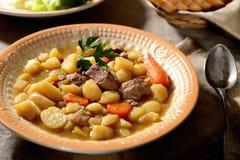 Rindereintopf, Kartoffeln und Grüns auf der ursprünglichen Serviette, Löffelweinlese Lizenzfreie Stockfotos