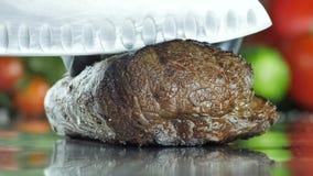 Rindfleisch geschnitten in große Stücke auf einer Metalloberfläche gegen einen Hintergrund des Gemüses stock video footage