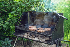 Rindfleisch- oder Schweinefleischgrillburger für den zugebereiteten Hamburger grillten auf bbq-Rauchgrill im Garten Stockfoto