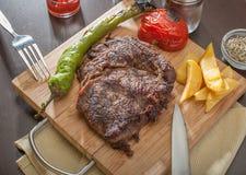 Rindfleisch-Steak diente mit gegrillten Tomaten und Pfeffern lizenzfreie stockfotos