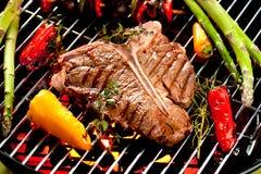 Rindfleisch-T-Bone-Steaks auf dem Grill mit Flammen lizenzfreie stockbilder