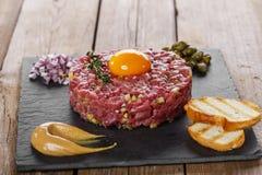 Rindfleisch tartare mit Kaprioleneigelb stockfotos