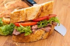 Rindfleischsandwich auf Ausschnittvorstand mit Messer. Stockbilder