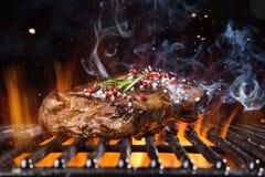 Rindfleischsteak auf dem Grill mit Flammen lizenzfreie stockfotos
