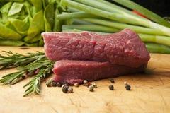Rindfleischsteak auf einem hölzernen Brett, Abschluss oben Stockfotografie
