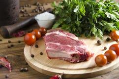 Rindfleischsteak auf einem hölzernen Brett auf einem hölzernen Hintergrund Lizenzfreies Stockfoto