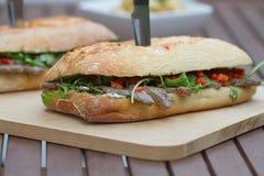 Rindfleischsteak auf einer gerösteten Stangenbrotbrotrolle, mit Käse der Ziege, Spinat und gegrillter Zwiebel Lizenzfreie Stockfotografie
