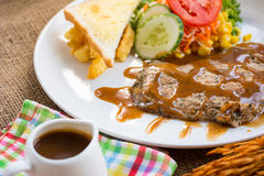 Rindfleischsteak mit Soße des schwarzen Pfeffers, Salat und Pommes-Frites auf s Lizenzfreies Stockfoto
