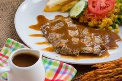 Rindfleischsteak mit Soße des schwarzen Pfeffers, Salat und Pommes-Frites auf s Stockbilder