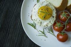 Rindfleischsteak mit Spiegelei in den Gew?rzen Verziert mit Rosmarin, frischer Kirsche und Scheiben brot Archiviert auf einer wei lizenzfreie stockbilder