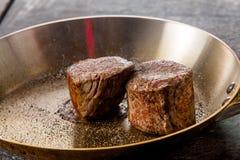 Rindfleischsteaks werden in einer Bratpfanne in einem Restaurant gebraten lizenzfreies stockbild