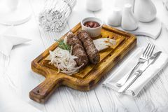 Rindfleischwürste mit Zwiebeln und Tomatendip auf einem Brett stockfotos