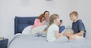 Rindo parents o vídeo do película das crianças que sentam-se junto na cama no quarto que fala, família feliz que passa o tempo vídeos de arquivo