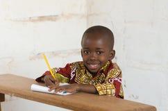 Rindo pouco menino de escola africano que senta-se na mesa que sorri no Ca imagem de stock