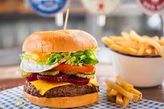 Rinforzi l'hamburger con formaggio, lattuga, il pomodoro, la barbabietola & il sottaceto, completati con un uovo fritto fotografia stock