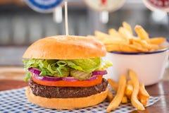 Rinforzi l'hamburger con lattuga, le cipolle, i sottaceti & il pomodoro fotografie stock libere da diritti