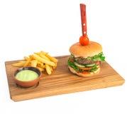 Rinforzi l'hamburger sul piatto di legno con la patata fritta Immagine Stock Libera da Diritti