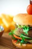 Rinforzi l'hamburger sul piatto di legno con la patata fritta Fotografia Stock Libera da Diritti