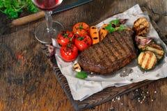 Rinforzi la bistecca arrostita con le verdure arrostite ed il vino rosso Fotografia Stock Libera da Diritti