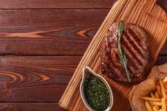 Rinforzi la bistecca del ribeye del barbecue con la salsa di chimichurri ed il francese fri Immagine Stock Libera da Diritti