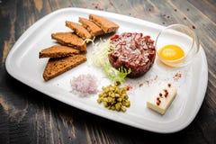 Rinforzi tartaro con la rucola insalata, il tuorlo d'uovo e le patatine fritte croccanti del pane sul piatto bianco Fotografie Stock