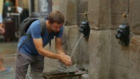 Rinfresco turistico maschio con acqua dalla fontana del cane a Bilbao, giro pedonale stock footage