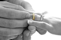 With this ring. Groom placing ring on brides hand Stock Images