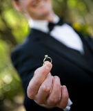 With this ring... Smiling groom, proudly holding a diamond solitaire ring out; selective focus on the ring Stock Photography
