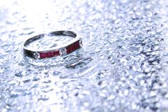 Ring 4. Ring with diamonds and rubys lying among water-drops Royalty Free Stock Images