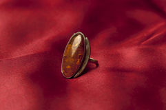Ring with amber. Amber ring isolated on red Stock Photography