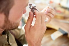 Ring Appraisal in Jewelry Shop. Closeup portrait of jeweler inspecting ring through magnifying glass in workshop Stock Photo