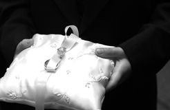 A ring bearer holding the ring. A ring bearer holding the pillow with the rings for the ceremony. Only showing the pillow and hands Stock Photo