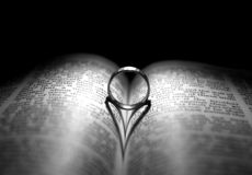 Ring and bible. Wedding Ring and heart shaped shadow over a Bible Stock Images