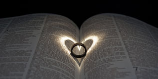 Ring Bible Heart. Wooden Ring on Bible with Heart Spotlight Stock Photos