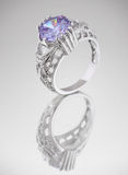Ring with blue gem on grey. Background Royalty Free Stock Images